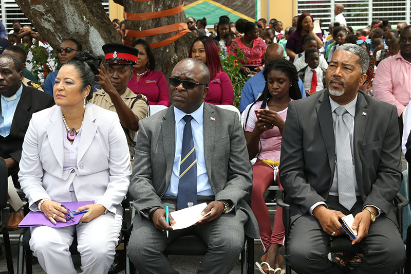 Minister of Transport and Local Government, the Hon. Frankie Campbell (seated right) listens to a medley of island songs performed by the Sandilands Primary School Choir. Also pictured, Sandilands Primary School Headmistress, Esther Cartwright, and former Sandilands Primary School student, and honouree, Captain Dwain Hutchinson. (BIS Photos/Raymond A. Bethel, Sr.)