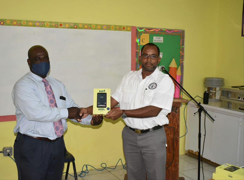 IMS president Kendall Williamson makes an official donation of 15 tablets to principal Demetrius Wildgoose. The tablets will be used to further the digital learning opportunities for senior students at the Louise McDonald high school
