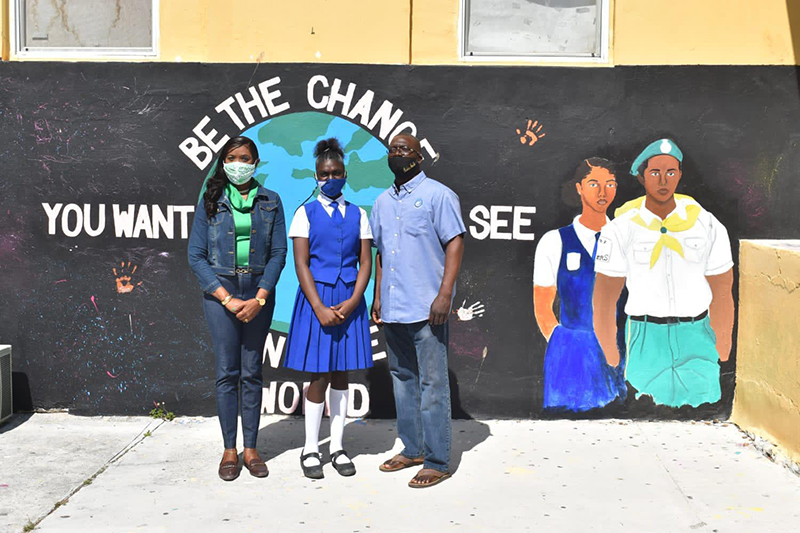 Island Administrator Deidre Fox and chief councilor Robbie Smith pose alongside student Antoneya Bowleg at ceremonies held to mark the donation of 15 new laptops to the high school