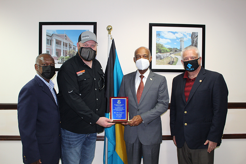 Minister of Education, the Honourable, Jeffrey Lloyd, presents Valencia College's, Construction Program Manager, Mark Hughes with a plaque in gratitude for his certification training efforts with the Bahamas Technical and Vocational Institute (BTVI). Mr. Hughes is a National Center for Construction Education and Research (NCCER) Master Trainer. Pictured from left to right are BTVI's Chairman, Kevin Basden; Mr. Hughes; Minister Lloyd and BTVI's President, Dr. Robert W. Robertson.