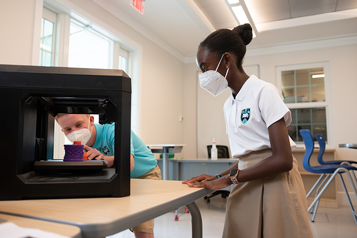 Students inspect 3D printed models in the Physics Classroom at the new LCIS Upper School campus.