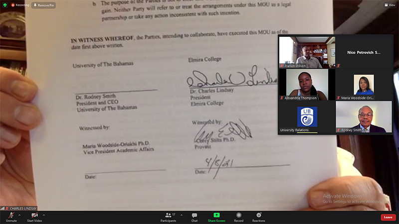Dr. Charles Lindsay holds up a copy of the MOU signed by Elmira College